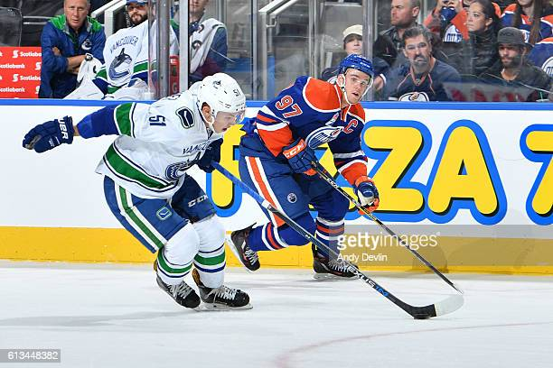 Connor McDavid of the Edmonton Oilers battles for the puck against Troy Stecher of the Vancouver Canucks on October 8 2016 at Rogers Place in...