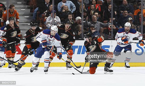 Connor McDavid of the Edmonton Oilers battles for the puck against Logan Shaw Hampus Lindholm and Ryan Kesler of the Anaheim Ducks during the game on...