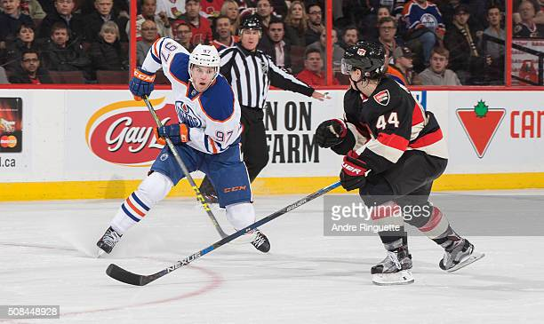 Connor McDavid of the Edmonton Oilers controls the puck against JeanGabriel Pageau of the Ottawa Senators at Canadian Tire Centre on February 4 2016...