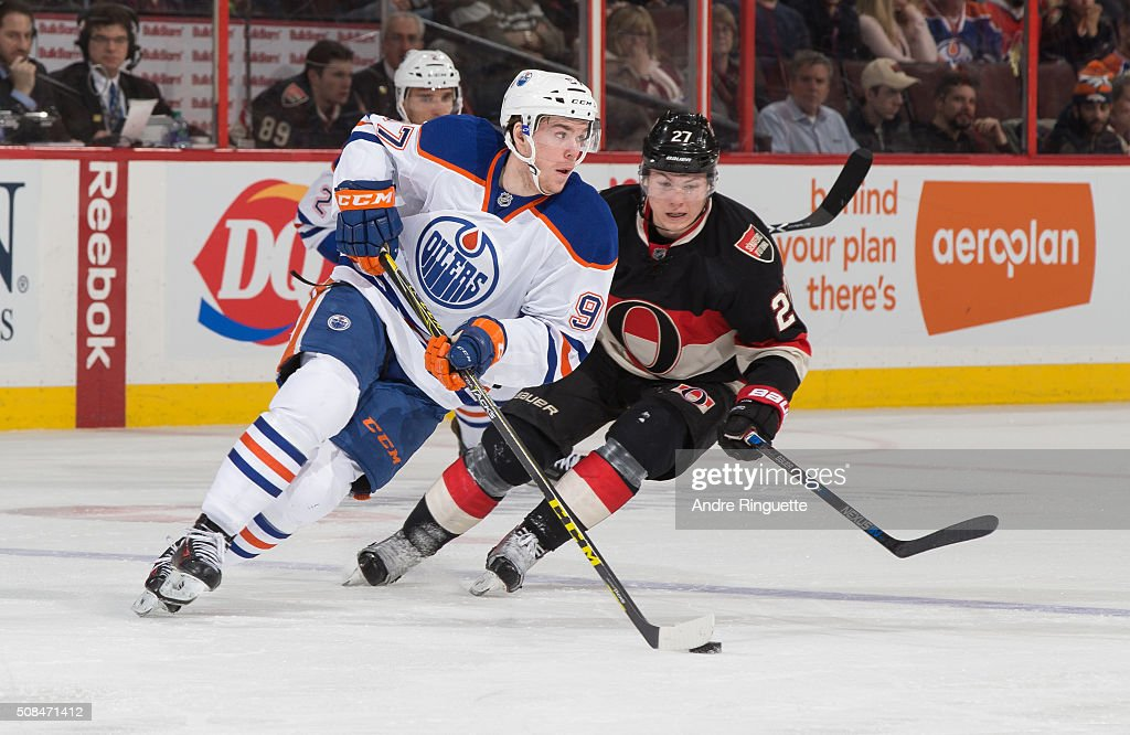 Connor McDavid #97 of the Edmonton Oilers controls the puck against Curtis Lazar #27 of the Ottawa Senators at Canadian Tire Centre on February 4, 2016 in Ottawa, Ontario, Canada.