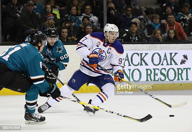 Connor McDavid of the Edmonton Oilers controls the puck while covered by Justin Braun and Chris Tierney of the San Jose Sharks at SAP Center on...