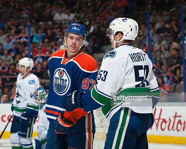 Connor McDavid of the Edmonton Oilers exchanges words with Bo Horvat of the Vancouver Canucks on October 1 2015 at Rexall Place in Edmonton Alberta...