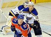 Connor McDavid of the Edmonton Oilers is checked by Jay Bouwmeester of the St Louis Blues at Rexall Place on October 15 2015 in Edmonton Alberta...