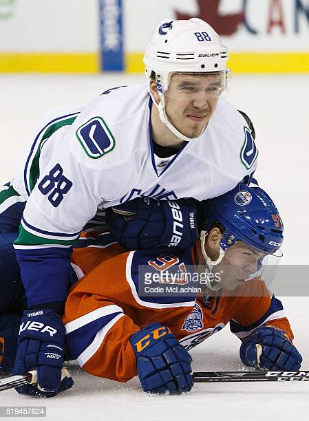 Connor McDavid of the Edmonton Oilers is flattened by Nikita Tryamkin of the Vancouver Canucks on April 6 2016 at Rexall Place in Edmonton Alberta...