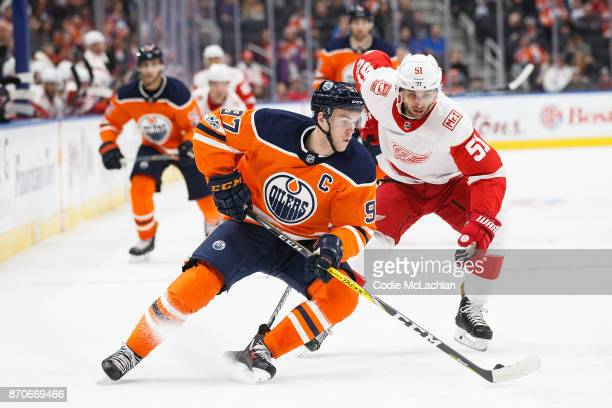 Connor McDavid of the Edmonton Oilers is pursued by Frans Nielsen of the Detroit Red Wings at Rogers Place on November 5 2017 in Edmonton Canada