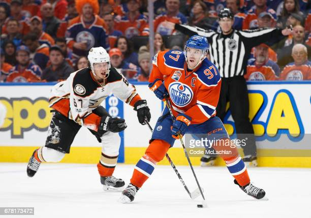 Connor McDavid of the Edmonton Oilers is pursued by Rickard Rakell of the Anaheim Ducks in Game Four of the Western Conference Second Round during...