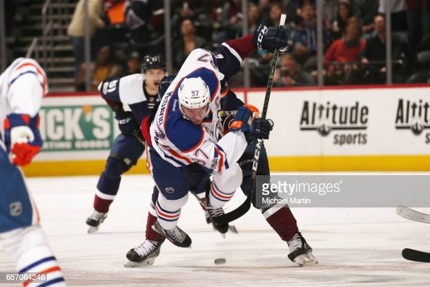 Connor McDavid of the Edmonton Oilers is tripped up by Nathan MacKinnon of the Colorado Avalanche at the Pepsi Center on March 23 2017 in Denver...