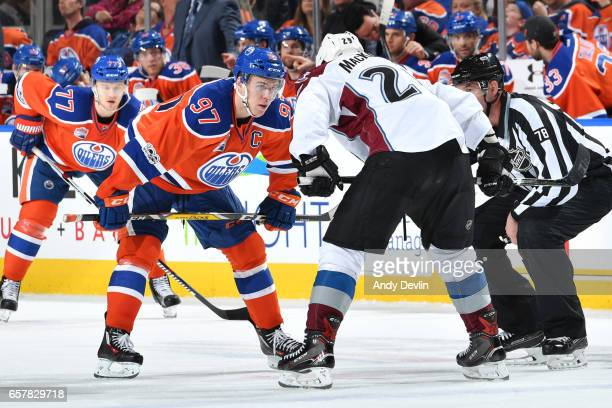 Connor McDavid of the Edmonton Oilers lines up for a face off against Nathan MacKinnon the Colorado Avalanche on March 25 2017 at Rogers Place in...