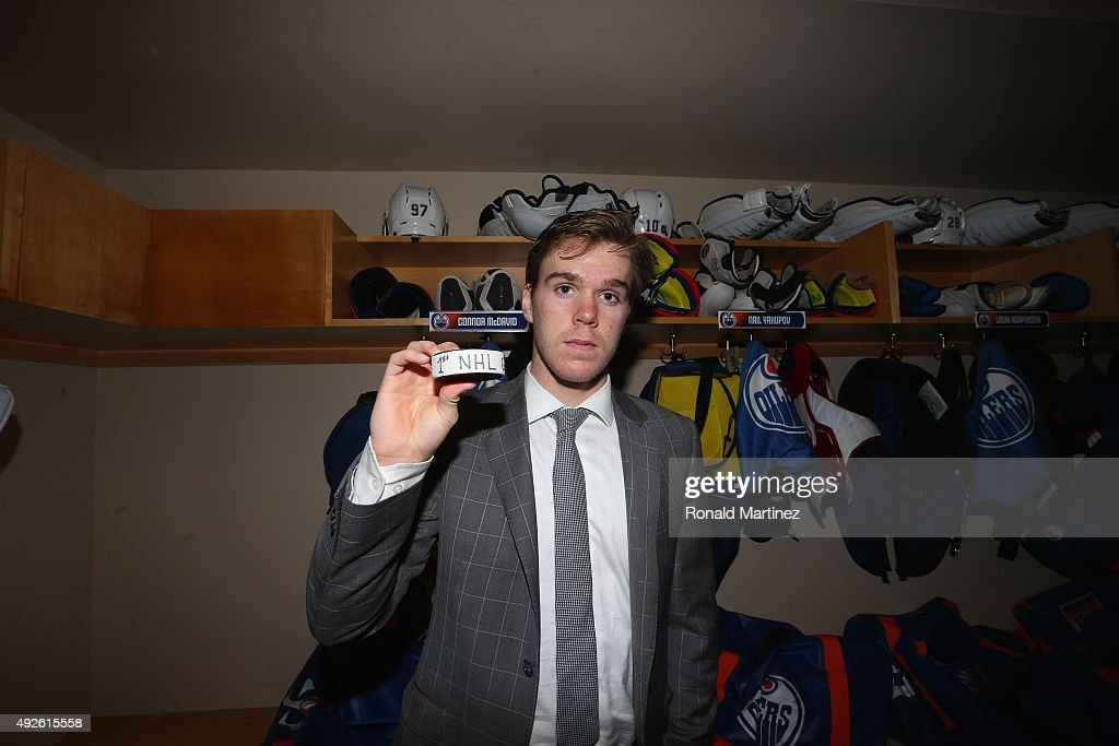 Connor McDavid #97 of the Edmonton Oilers poses for a photo with his first career NHL goal puck at American Airlines Center on October 13, 2015 in Dallas, Texas.