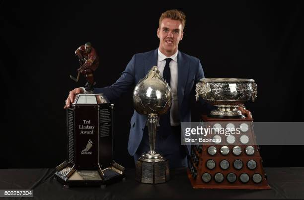 Connor McDavid of the Edmonton Oilers poses for a portrait with the from left to right Ted Lindsay Award Hart Memorial Trophy and the Art Ross Trophy...
