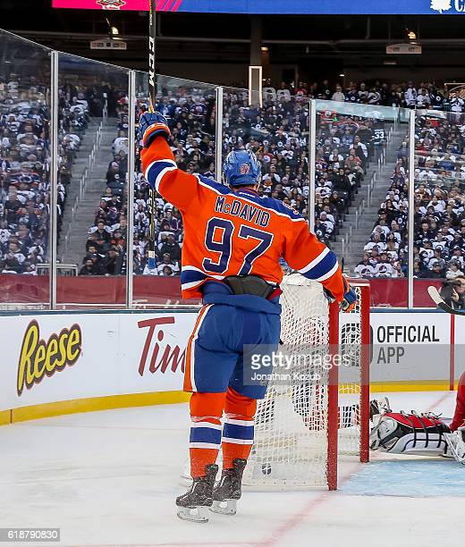 Connor McDavid of the Edmonton Oilers raises his stick in celebration of a second period goal by teammate Darnell Nurse against the Winnipeg Jets in...