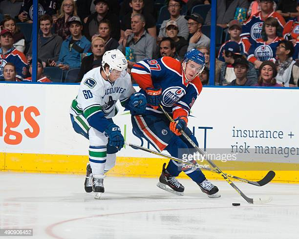 Connor McDavid of the Edmonton Oilers skates on the ice while being pursued by Ben Hutton of the Vancouver Canucks on October 1 2015 at Rexall Place...