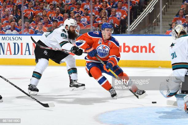 Connor McDavid of the Edmonton Oilers skates while being pursued by Brent Burns of the San Jose Sharks in Game One of the Western Conference First...