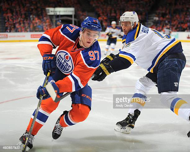 Connor McDavid of the Edmonton Oilers skates with the puck while being pursued by Jay Bouwmeester of St Louis Blues on October 15 2015 at Rexall...