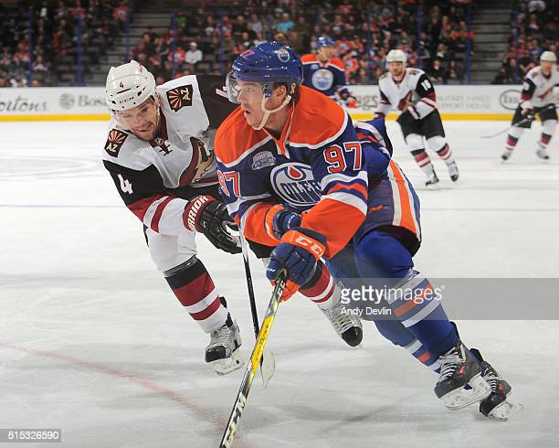 Connor McDavid of the Edmonton Oilers skates with the puck while being pursued by Zbynek Michalek of the Arizona Coyotes on March 12 2016 at Rexall...