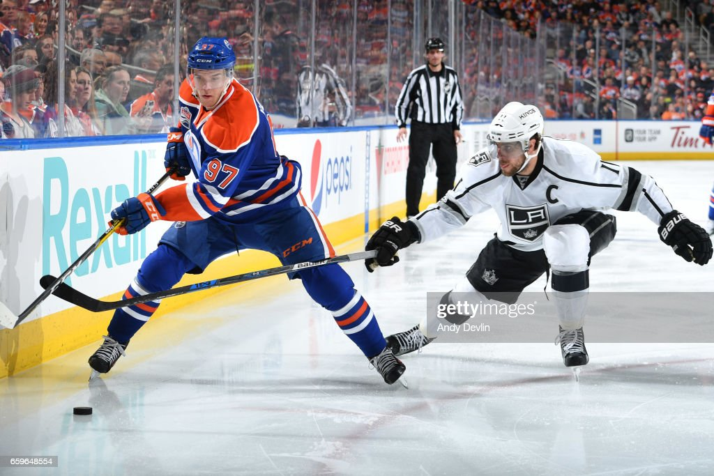Connor McDavid #97 of the Edmonton Oilers skates with the puck while being pursued by Anze Kopitar #11 of the Los Angeles Kings on March 28, 2017 at Rogers Place in Edmonton, Alberta, Canada.
