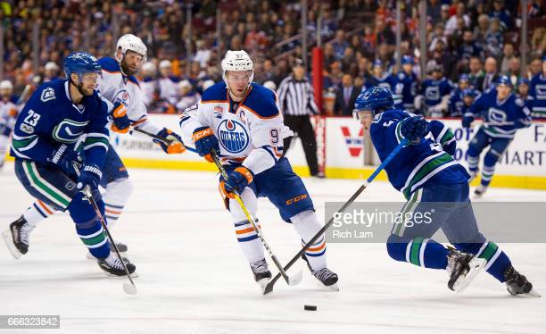 Connor McDavid of the Edmonton Oilers tires to slip between the defence of Alexander Edler and Troy Stecher of the Vancouver Canucks in NHL action on...