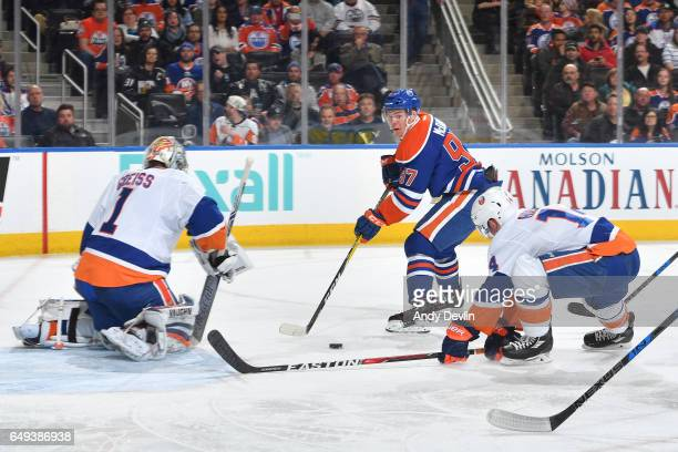 Connor McDavid of the Edmonton Oilers tries to pass the puck past Thomas Greiss and Thomas Hickey of the New York Islanders on March 7 2017 at Rogers...