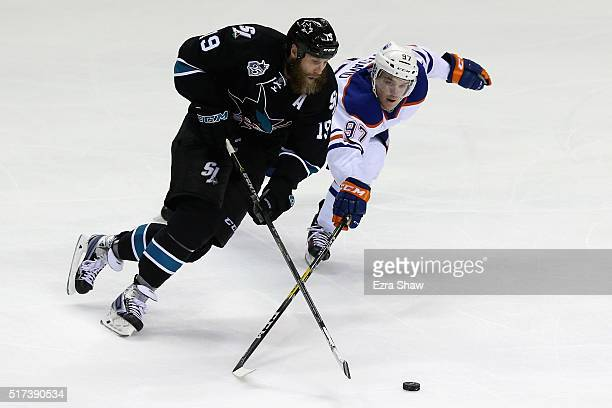 Connor McDavid of the Edmonton Oilers tries to steal the puck from Joe Thornton of the San Jose Sharks at SAP Center on March 24 2016 in San Jose...