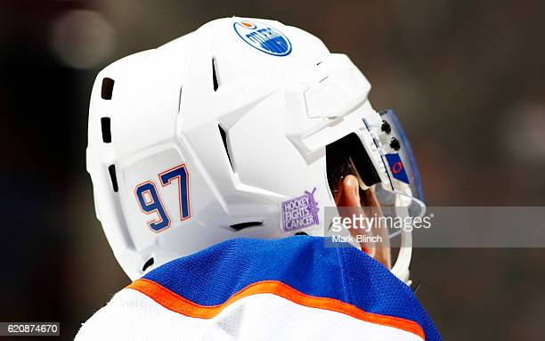 Connor McDavid of the Edmonton Oilers wears a helmet with the 'Hockey Fights Cancer' logo as his team plays the Toronto Maple Leafs during the third...
