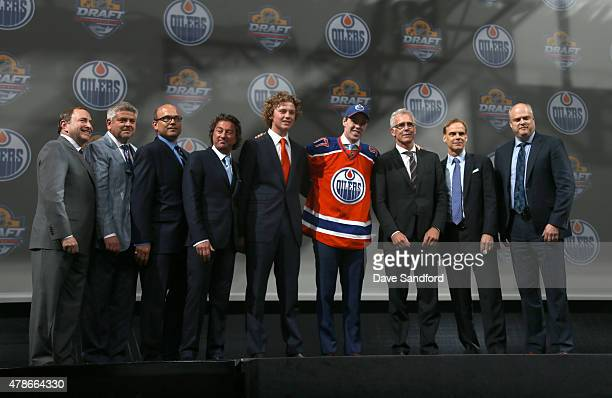 Connor McDavid poses on stage with team personnel after being selected first overall by the of the Edmonton Oilers during Round One of the 2015 NHL...