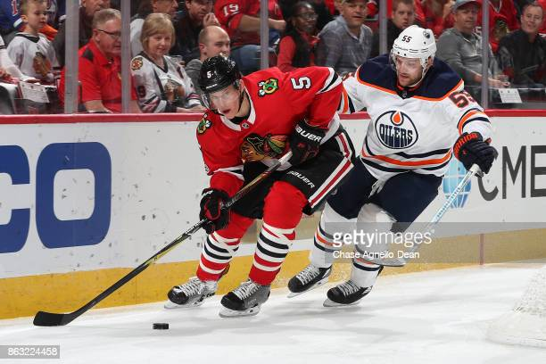 Connor Murphy of the Chicago Blackhawks and Mark Letestu of the Edmonton Oilers chase the puck in the first period at the United Center on October 19...