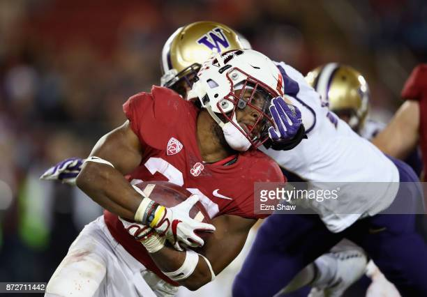 Connor O'Brien of the Washington Huskies tries to tackle Bryce Love of the Stanford Cardinal with a hand to the face at Stanford Stadium on November...