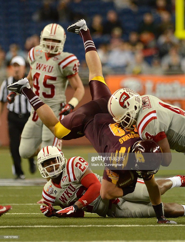 Connor Odykirk #89 of the Central Michigan University Chippewas is tackled by Andrew Jackson #4 of the Western Kentucky University Hilltoppers during the Little Caesars Pizza Bowl at Ford Field on December 26, 2012 in Detroit, Michigan. The Chippewas defeated the Hilltoppers 24-21.