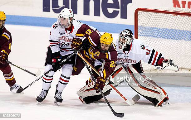 Connor Reilly of the Minnesota Golden Gophers is sandwiched between Ryan Ruck and Adam Gaudette both of the Northeastern Huskies during NCAA hockey...