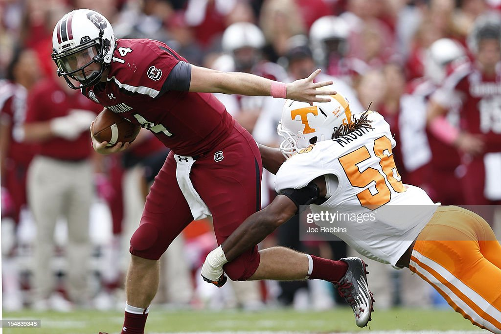 Connor Shaw #14 of the South Carolina Gamecocks tries to avoid Curt Maggitt #56 of the Tennessee Volunteers during the game at Williams-Brice Stadium on October 27, 2012 in Columbia, South Carolina. South Carolina won 38-35.