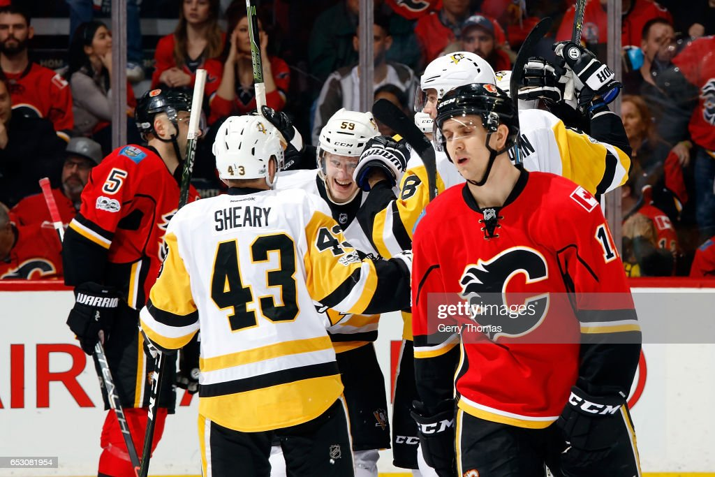 Connor Sheary #43, Jake Guentzel #59, and teammates of the Pittsburgh Penguins celebrate a goal against the Calgary Flames during an NHL game on March 13, 2017 at the Scotiabank Saddledome in Calgary, Alberta, Canada.