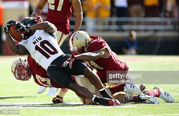 Connor Strachan of the Boston College Eagles and William Harris tackle Tommylee Lewis of the Northern Illinois Huskies during the second half at...