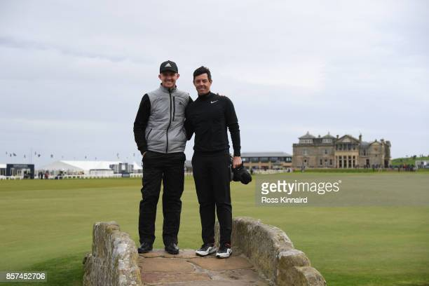 Connor Syme of Scotland and Rory McIlroy of Northern Ireland pose for photos on the Swilken Bridge during practice prior to the 2017 Alfred Dunhill...