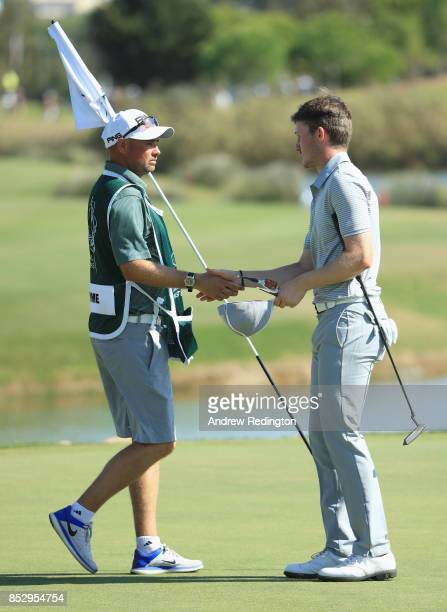 Connor Syme of Scotland shakes hands with his caddie on the 18th green during day four of the Portugal Masters at Dom Pedro Victoria Golf Club on...