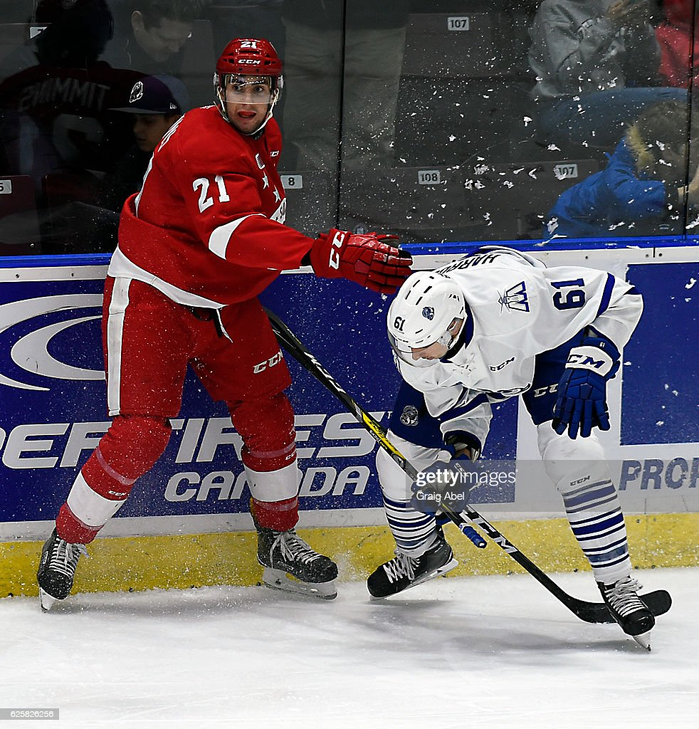 Connor Timmins #21 of the Sault Ste. Marie Greyhounds battles on the boards with Brendan Harrogate #61 of the Mississauga Steelheads during game action on November 25, 2016 at Hershey Centre in Mississauga, Ontario, Canada.