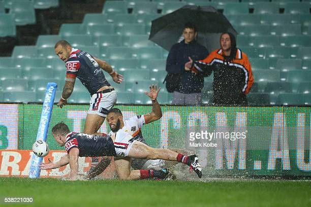 Connor Watson of the Roosters and Josh AddoCarr of the Tigers compete for the ball during the round 13 NRL match between the Sydney Roosters and the...