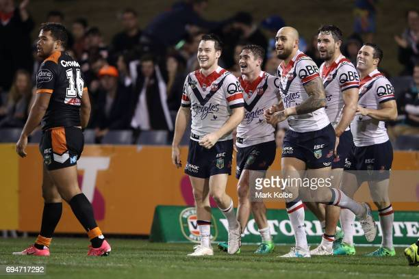 Connor Watson of the Roosters celebrates with his team mates after scoring a try during the round 14 NRL match between between the Wests Tigers and...