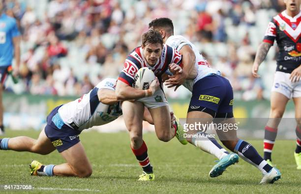 Connor Watson of the Roosters is tackeld by Keegan Hipgrave and Patrick Politoni of the Titans during the round 26 NRL match between the Sydney...