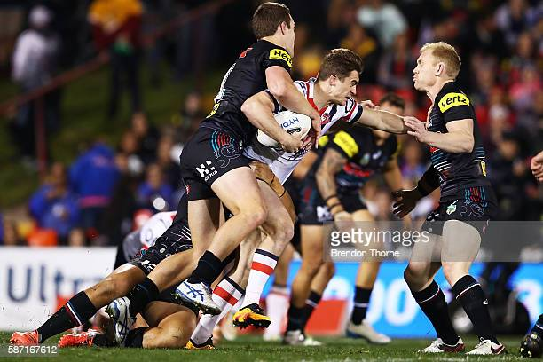 Connor Watson of the Roosters is tackled by the Panthers defence during the round 22 NRL match between the Penrith Panthers and the Sydney Roosters...