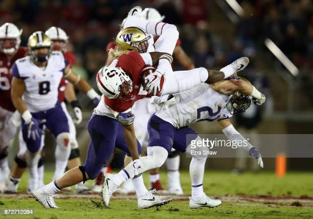Connor Wedington of the Stanford Cardinal goes over Taylor Rapp and Ben BurrKirven of the Washington Huskies during their game at Stanford Stadium on...