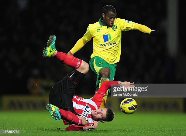 Connor Wickham of Sunderland falls to the pitch under challenge by Sebastien Bassong of Norwich City during the Barclays Premier League match between...