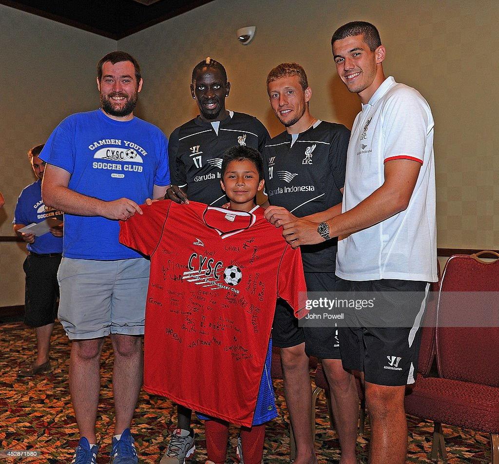 Conor Cody of Liverpool, Lucas of Liverpool and Mamadou Sakho of Liverpool were presented with a signed shirt by Barry Evans (L) and Jesus Colin of the Camden Youth Soccer Club when they visited the Liverpool Team Hotel in Princeton on July 28, 2014 in Princeton, New Jersey.