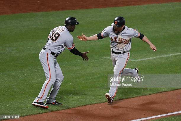Conor Gillaspie celebrates with third base coach Roberto Kelly of the San Francisco Giants as he runs the bases after hitting a threerun homerun in...