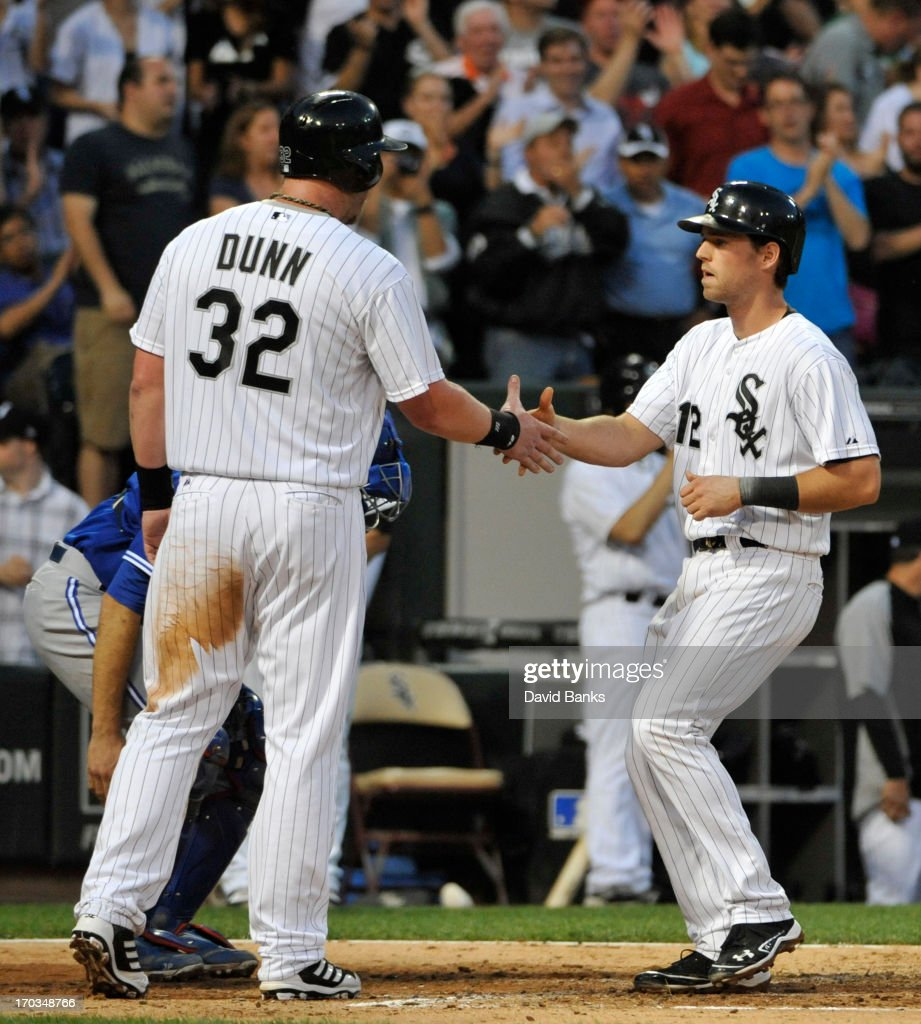 Conor Gillaspie #12 of the Chicago White Sox is greeted by Adam Dunn #32 after hitting a three-run homer against the Toronto Blue Jays during the fourth inning on June 11, 2013 at U.S. Cellular Field in Chicago, Illinois.