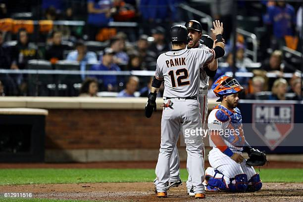 Conor Gillaspie of the San Francisco Giants celebrates with teammates Joe Panik and Brandon Crawford after hitting a threerun homerun in the ninth...