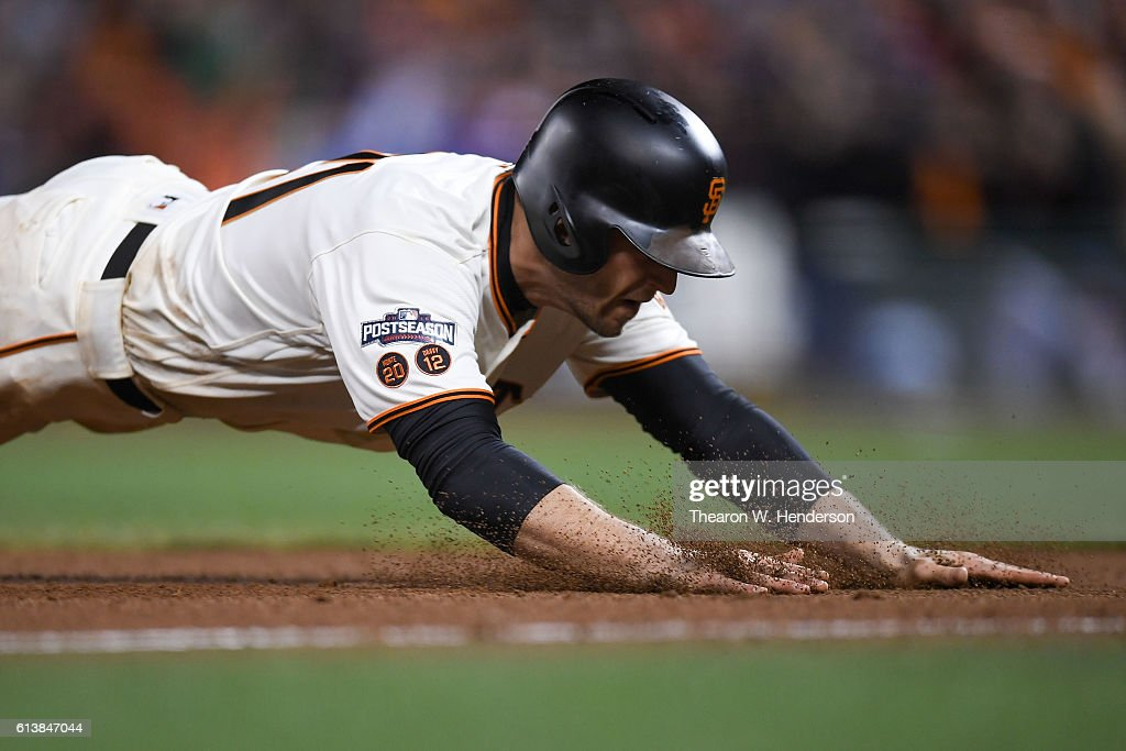 Conor Gillaspie #21 of the San Francisco Giants slides into third after hitting a two-run triple in the eighth inning against the Chicago Cubs during Game Three of their National League Division Series against the Chicago Cubs at AT&T Park on October 10, 2016 in San Francisco, California.