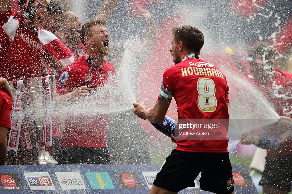 Conor Hourihane of Barnsley sprays champagne on his team mates as they celebrate promotion after winning the Sky Bet League One Play Off Final between Barnsley and Millwall at Wembley Stadium on May 29, 2016 in London, England.