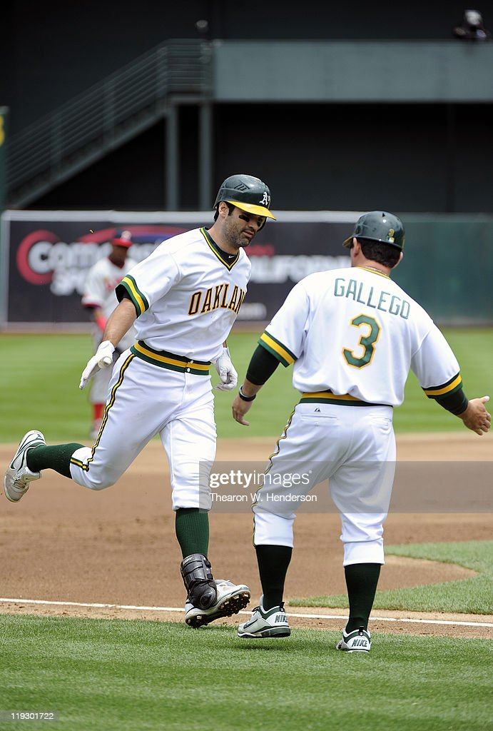<a gi-track='captionPersonalityLinkClicked' href=/galleries/search?phrase=Conor+Jackson&family=editorial&specificpeople=593147 ng-click='$event.stopPropagation()'>Conor Jackson</a> #28 of the Oakland Athletics hits a grand-slam and rounds third base to slap the hand of coach <a gi-track='captionPersonalityLinkClicked' href=/galleries/search?phrase=Mike+Gallego&family=editorial&specificpeople=836149 ng-click='$event.stopPropagation()'>Mike Gallego</a> #3 against the Los Angeles Angels of Anaheim in the first inning during an MLB baseball game at the O.co Coliseum July 17, 2011 in Oakland, California.