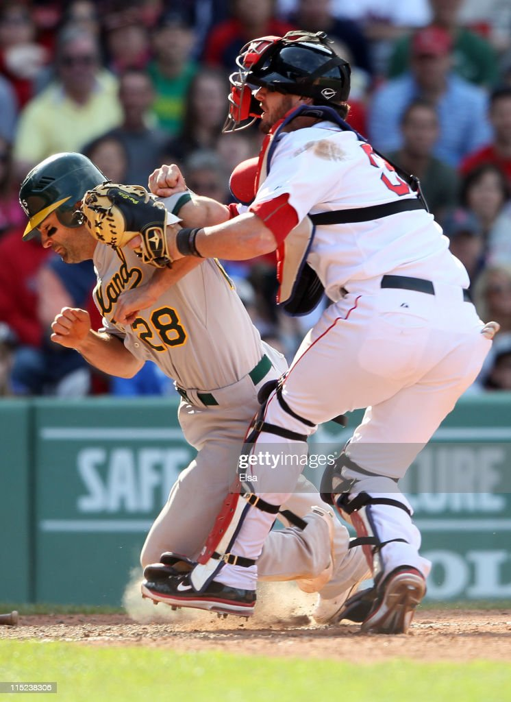 <a gi-track='captionPersonalityLinkClicked' href=/galleries/search?phrase=Conor+Jackson&family=editorial&specificpeople=593147 ng-click='$event.stopPropagation()'>Conor Jackson</a> #28 of the Oakland Athletics is tagged out by <a gi-track='captionPersonalityLinkClicked' href=/galleries/search?phrase=Jarrod+Saltalamacchia&family=editorial&specificpeople=836404 ng-click='$event.stopPropagation()'>Jarrod Saltalamacchia</a> #39 of the Boston Red Sox in the 11th inning on June 4, 2011 at Fenway Park in Boston, Massachusetts.