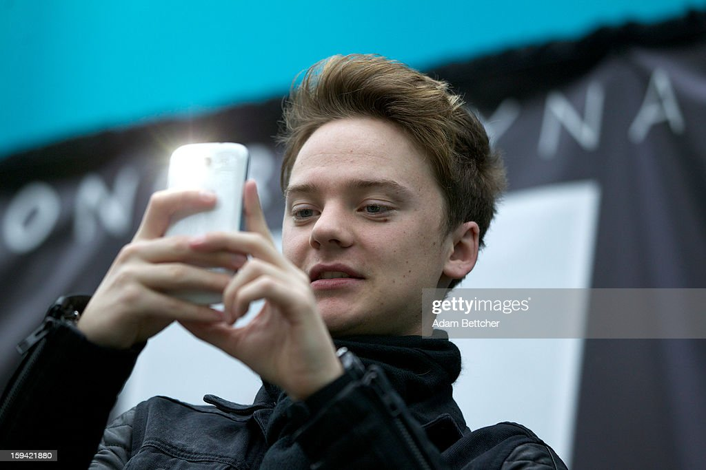 Conor Maynard takes a photo with his cell phone while performing at the Mall of America on January 13, 2013 in Bloomington, Minnesota.